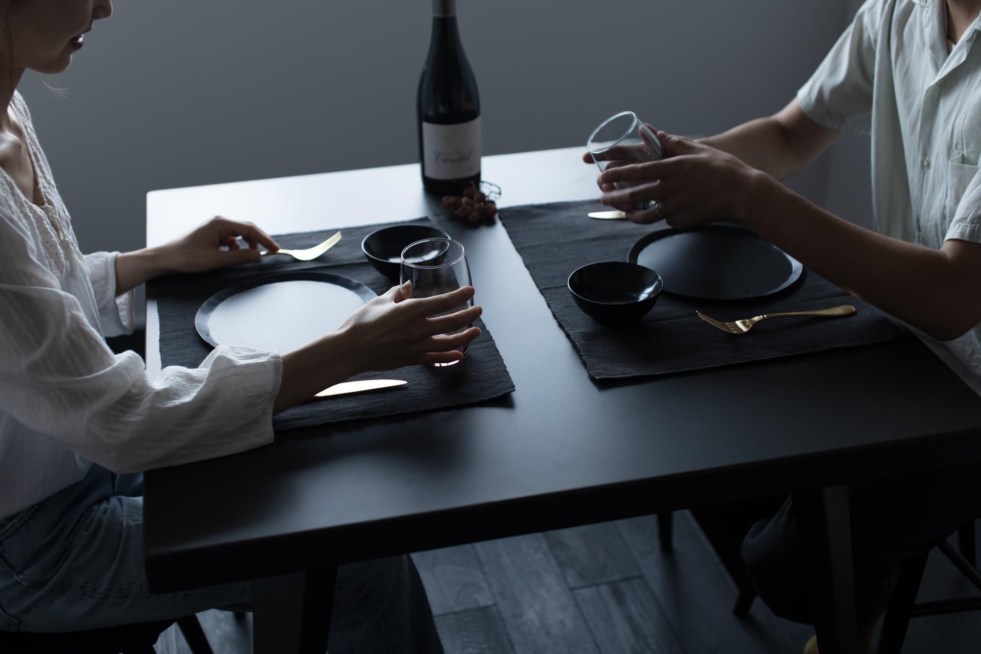 レジデンス此花 モデルルーム / ダイニングテーブルと夫婦の手元